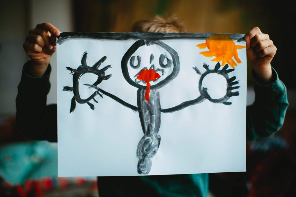 kid holding up a drawing