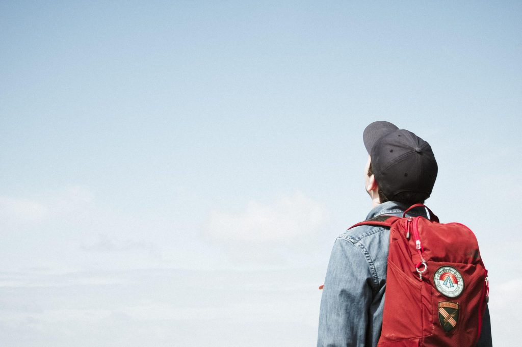 student wearing backpack looking at the sky